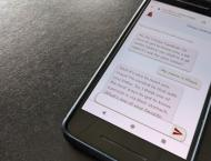 A phone on a desk displays a text chat with Chirpy, a Stanford chatbot.