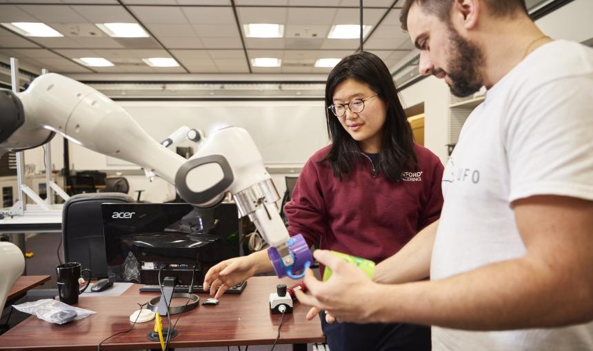 Two researchers, a woman and a man, work on a robotic arm.