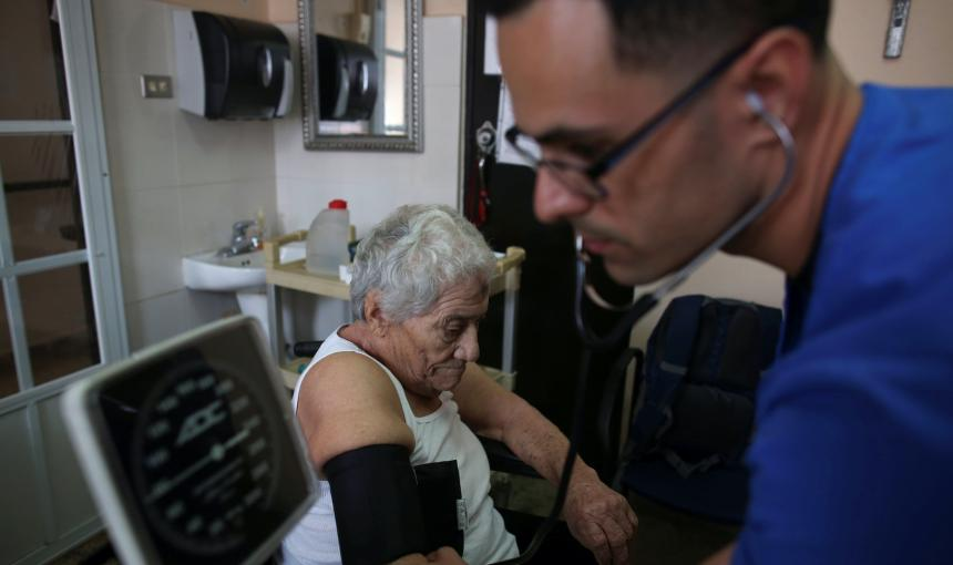 A nurse takes the blood pressure of a patient during a home check-up.