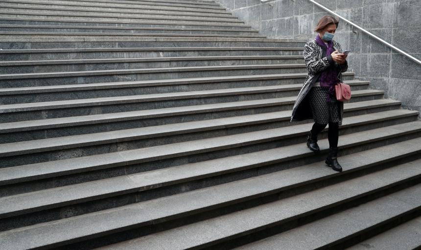 A woman walks down a lonely set of stairs while staring at her phone.
