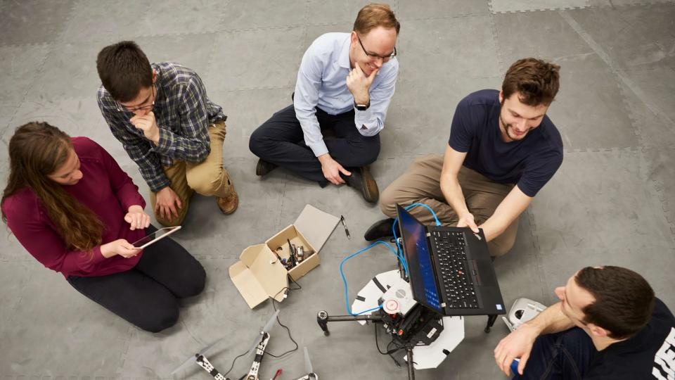 circle of 5 students working on a computer-controlled drone together