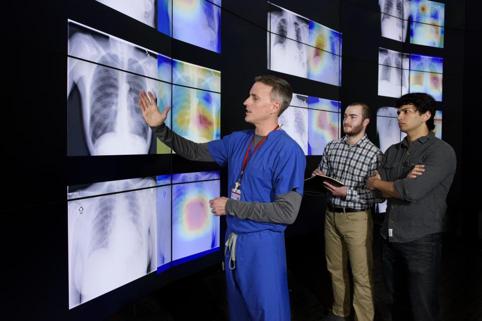 Radiologist Matthew Lungren, left, meets with graduate students Jeremy Irvin and Pranav Rajpurkar to discuss the results of detections made by the algorithm.