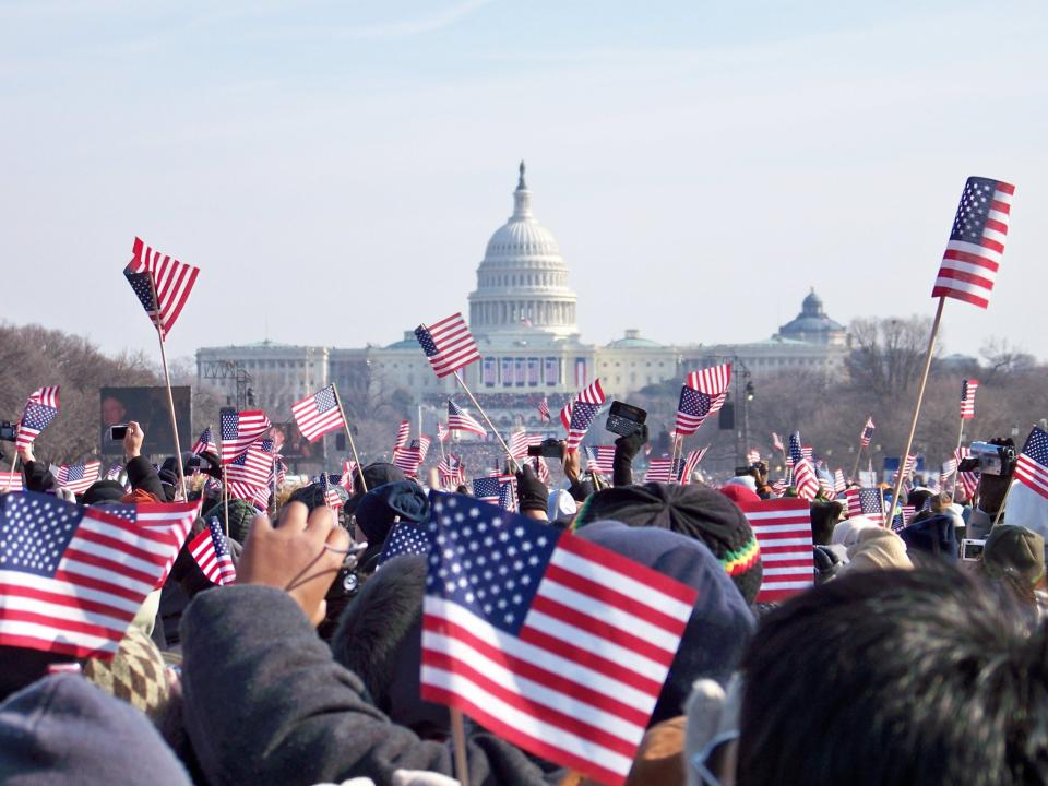 Attendees at a U.S. presidential inauguration wave flags with the Capitol Building in the background.