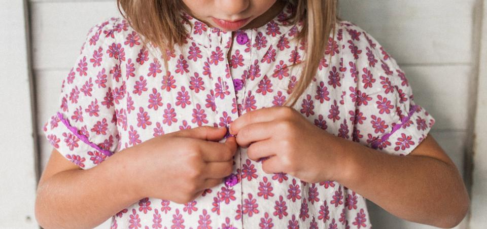 A child buttons her brightly colored flowered shirt