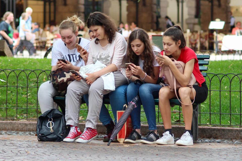 Young women line a park bench, each engrossed in her smartphone.