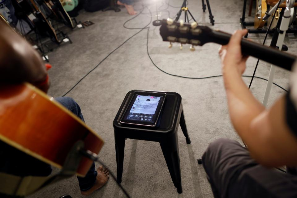 Guitarists perform with a computer tablet set up to help them record and stream.